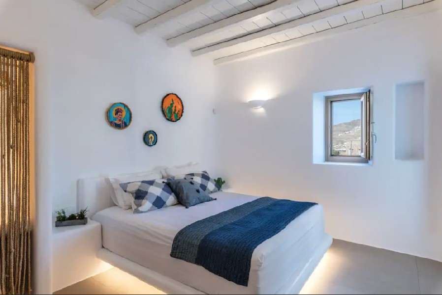 white wall and lighted bedroom with soft bed and pillows