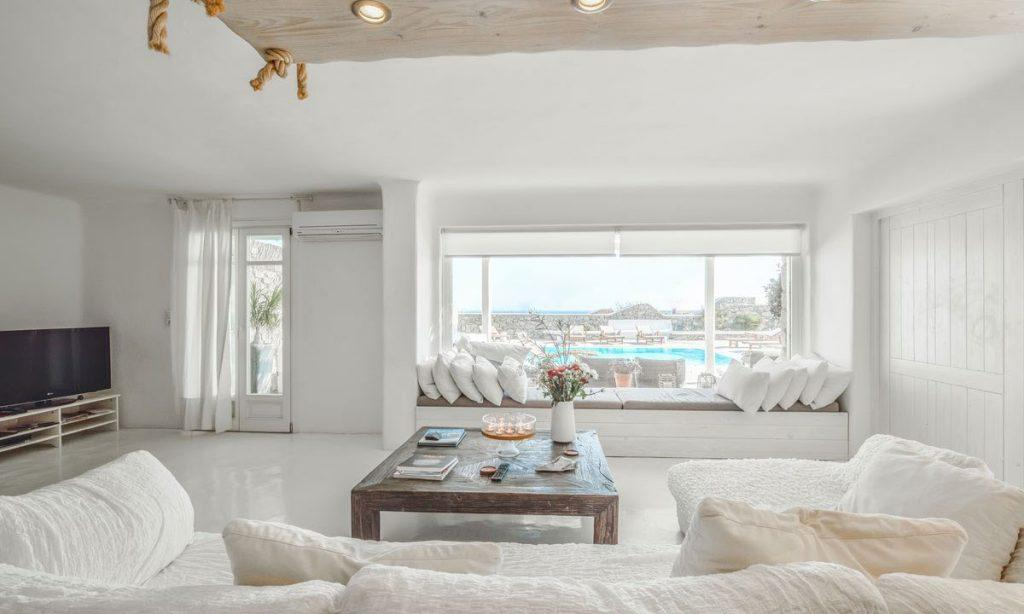 Villa-Aeneas-1_12.jpg Super Paradise Mykonos, living room, flat screen TV, curtain, AC, sofa, pillows, table, vase, flowers