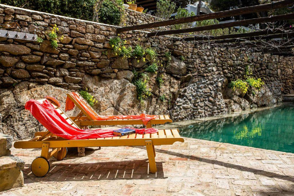 outdoor rocky area with pool and colorful flowers