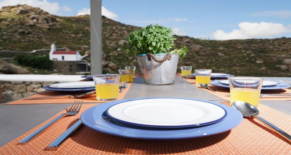 Villa-Futura_12.jpg Pirgi Mykonos Outdoor Dining area, plate, fork, spoon, knife, flowers