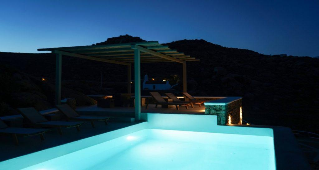 outdoor area with illuminated pool and climbers