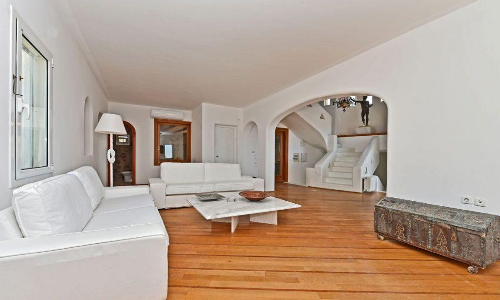 spacious living area with wooden floor and stairs to second level
