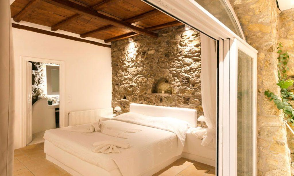 bedroom with rock wall and private bathroom