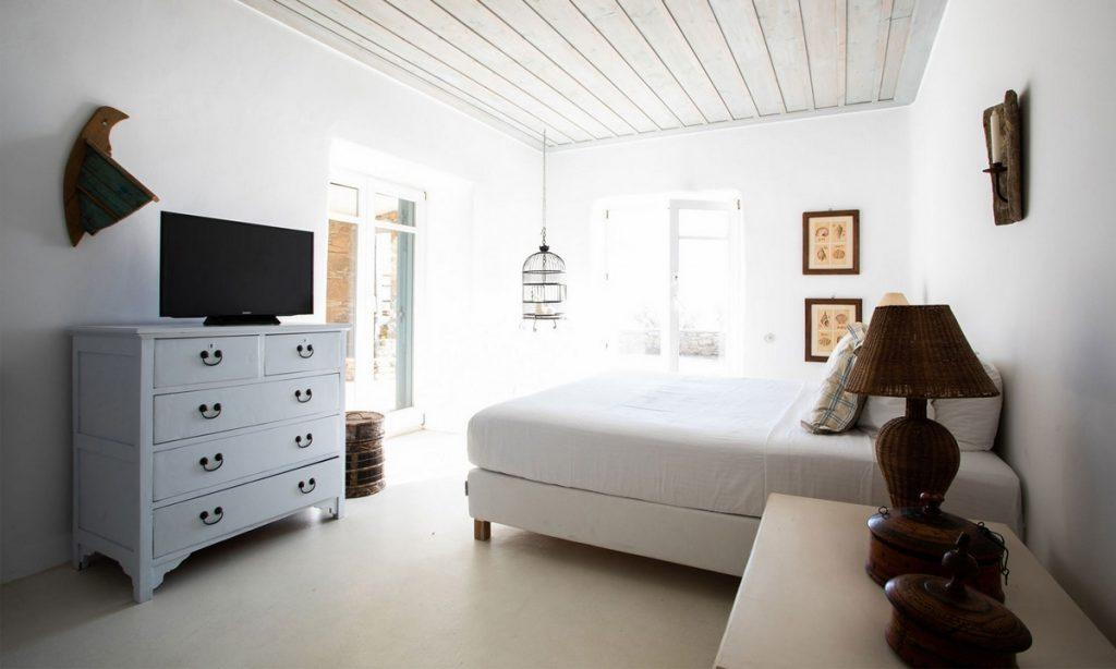 white wall bedroom with cozy bed and lighting coming from the window