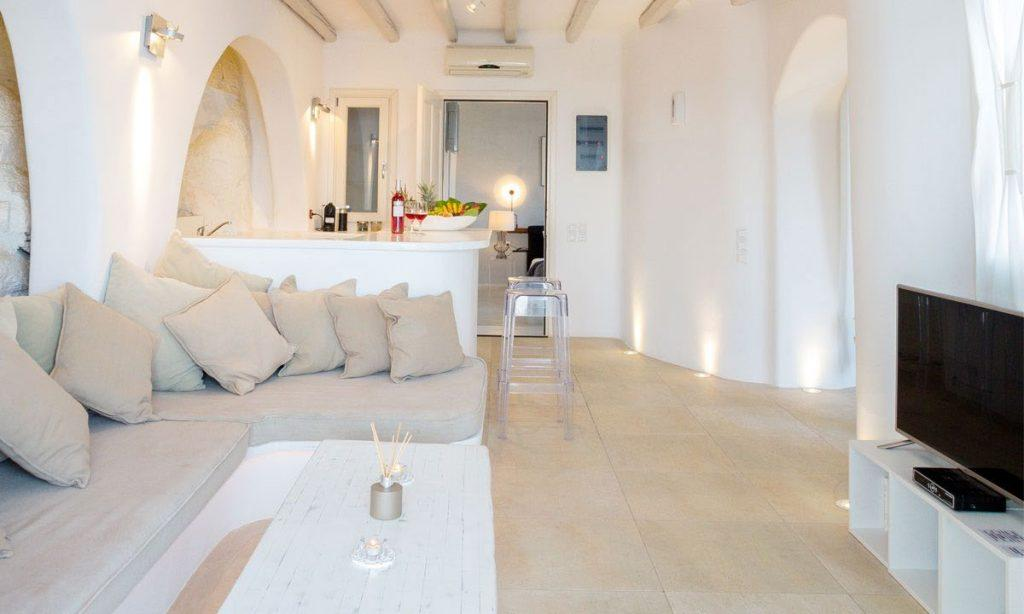 Villa Ida, Super Paradise, Mykonos, Pillows, Curtains, Stone wall, Door, Table, Lamps, Living room, Kitchen, Flat screen TV, Chairs, Fruits, Door