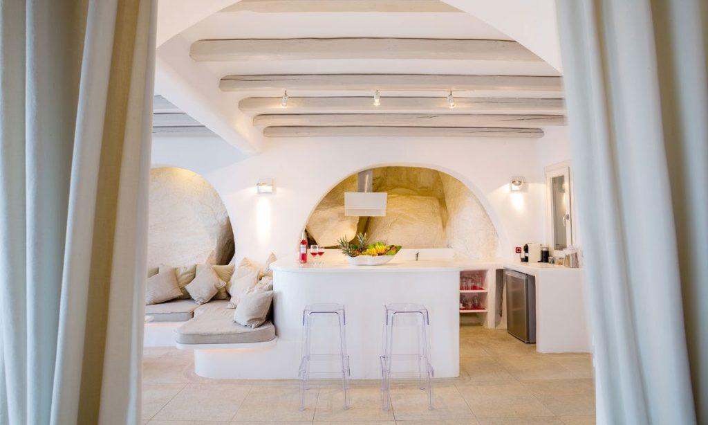 Villa Ida, Super Paradise, Mykonos, Pillows, Curtains, Stone wall, Door, Table, Lamps, Living room, Kitchen, Refrigerator, Chairs, Fruits
