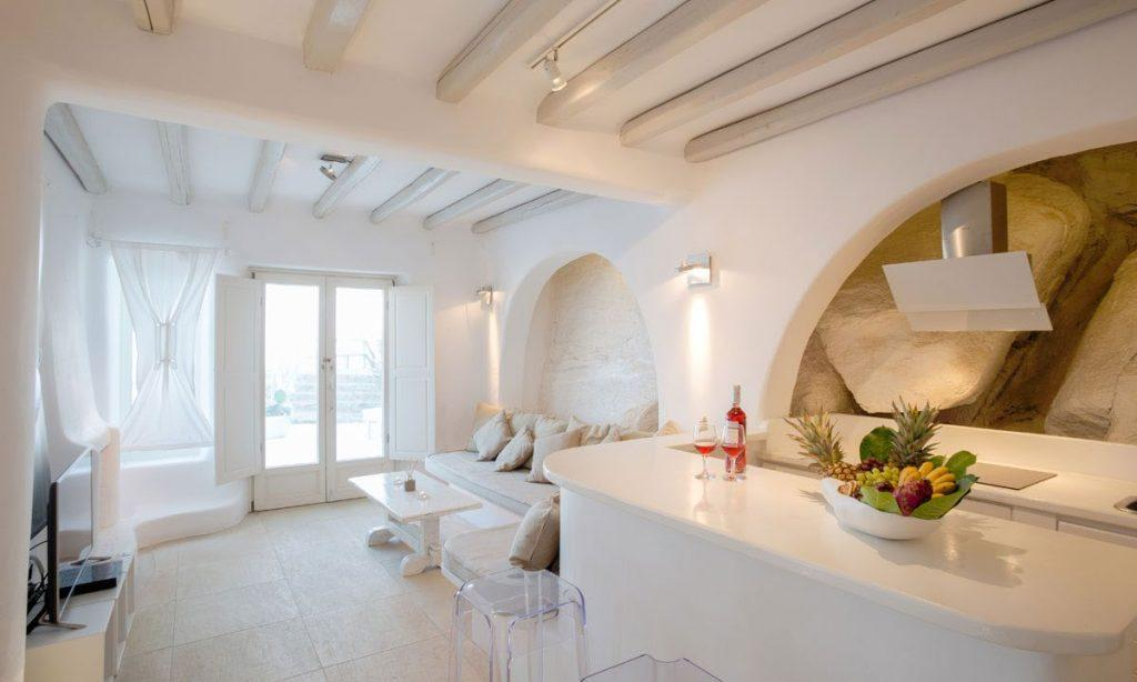 Villa Ida, Super Paradise, Mykonos, Pillows, Curtains, Stone wall, Door, Table, Lamps, Living room, Kitchen, Flat screen TV, Chairs, Fruits, Door, Outdoor view