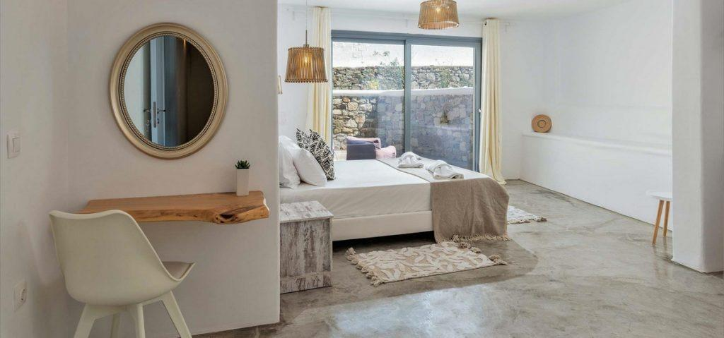 white wall bedroom with round mirror and night table