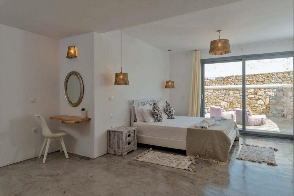 bedroom with lit lamps and white chair in the corner