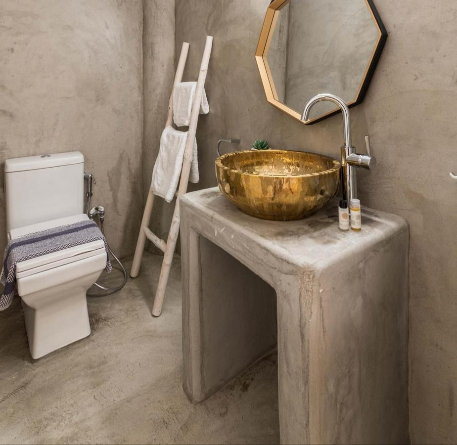 simply designed bathroom with gold sink and toilet