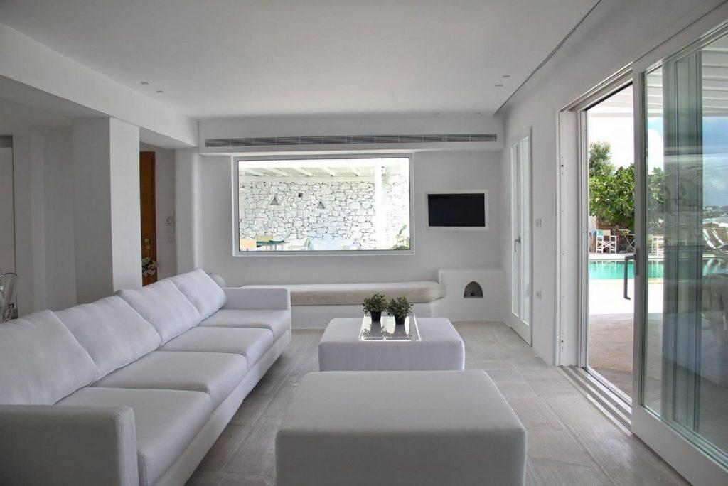 perfectly designed white living room with glass balcony door and soft bed