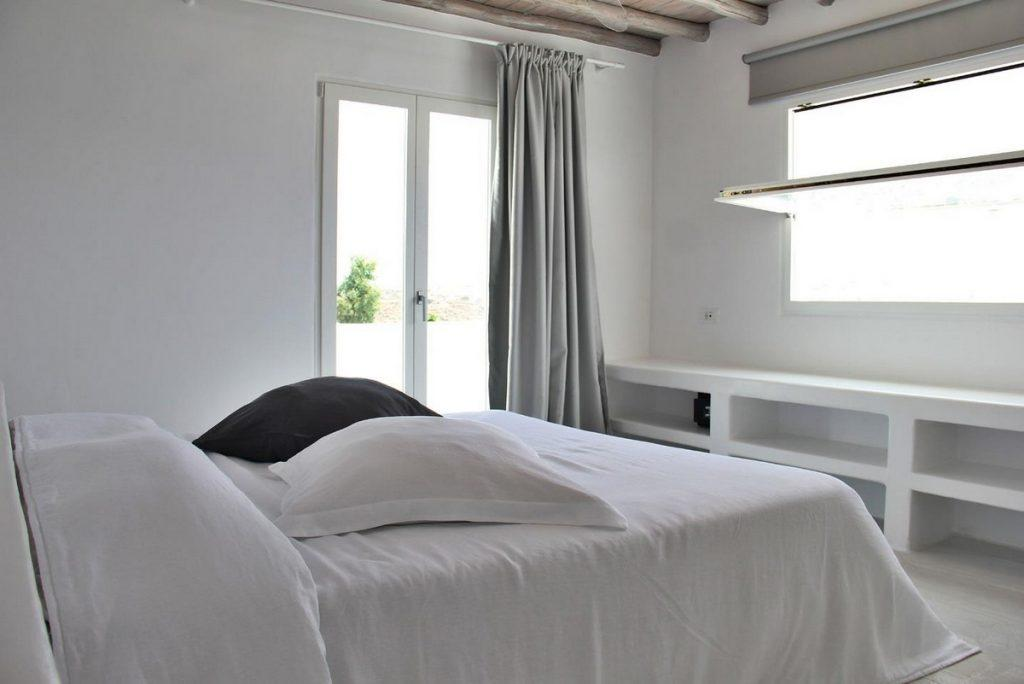 white bedroom with cozy bed and soft pillows with daylight from window and terrace