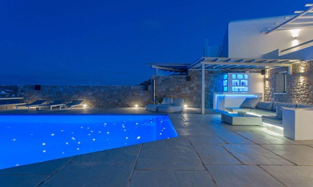 beautifully lit pool as well as villa walls