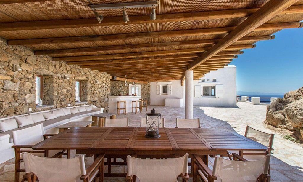 Villa-Kyros_09.jpg Super Paradise Mykonos, outdoor dining area, dining table, climbers, sofa, pillows, bar, stone, sky, sea