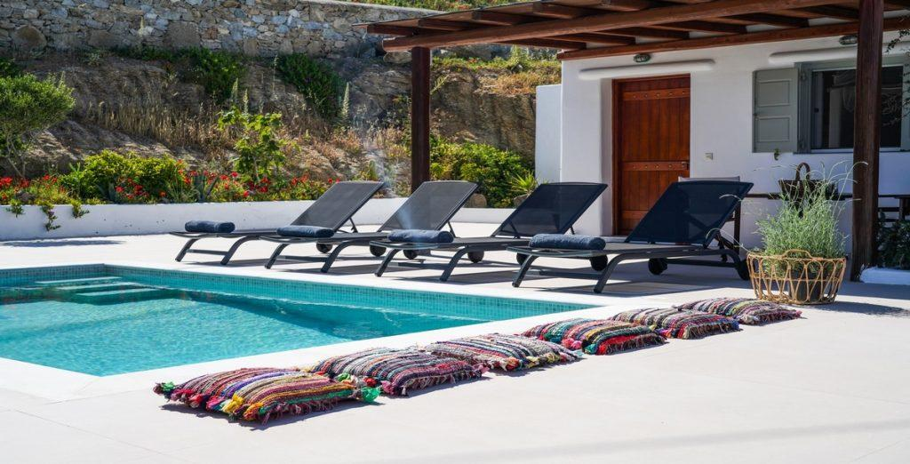 outdoor area with pool and colorful pillows