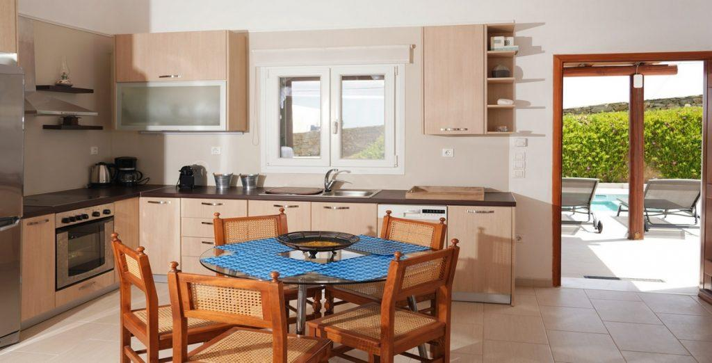 fully equipped kitchen with wooden cabins and glass table