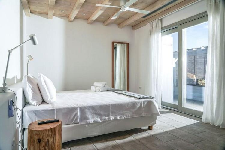white wall bedroom with huge cozy bed and fan