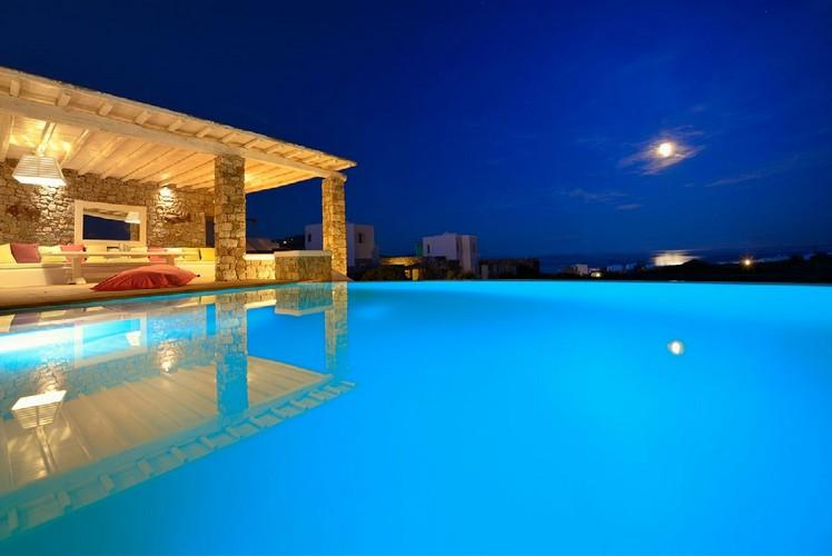 outdoor area with illuminated and infinity pool