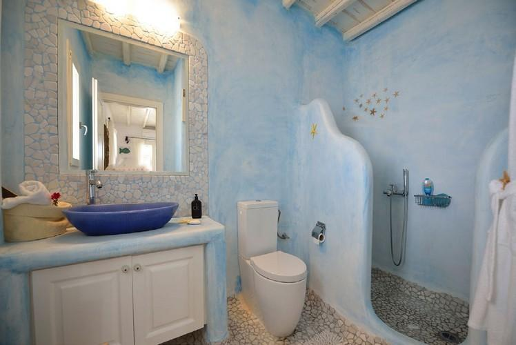 blue wall bathroom with lit mirror and shower