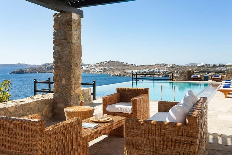 Villa_Miya10_21.jpg Agios Lazaros Mykonos Outdoor Living area, chairs, bed, pillows, table, candle, pool