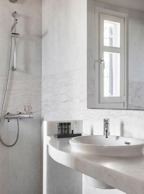 bathroom with grey and tiled walls and huge mirror