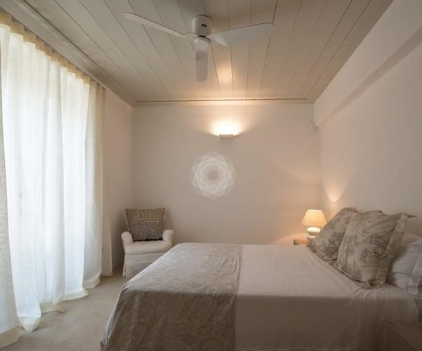Villa_Ophelia_08.jpg Agios Lazaros Mykonos 1st Bedroom, double bed, pillows, fan, chair, night table, curtains