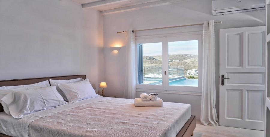 Villa_Sofy_22.jpg Kalafatis Mykonos 1st Bedroom, bed, pillows, towels, door, air condition, curtains, windows, night table, lamp