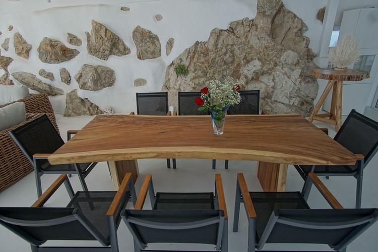 dining area with lovely designed table and and rock wall