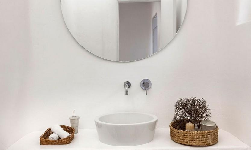 white wall bathroom with round mirror and ceramic sink