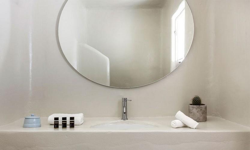 bathroom with huge round mirror and ceramic plate