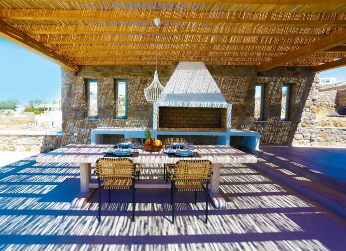 Villa_Yanni_10.jpg Fanari Mykonos Outdoor Dining area, table, chairs, fireplace, plate, glass, lamp