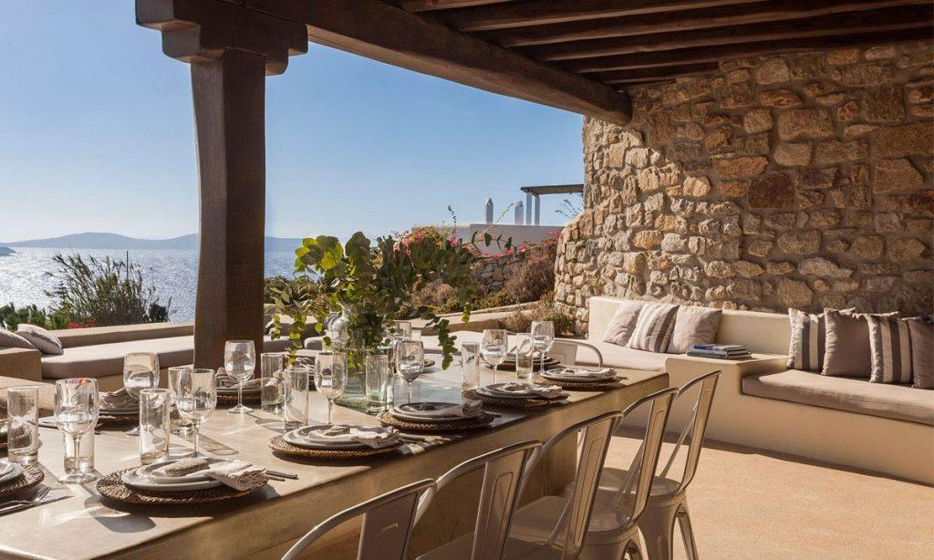 Villa-Agda_15.jpg Agios Ioannis Mykonos, outdoor dining area, dining table, plates, glasses, chairs, sofa, pillows, stone wall