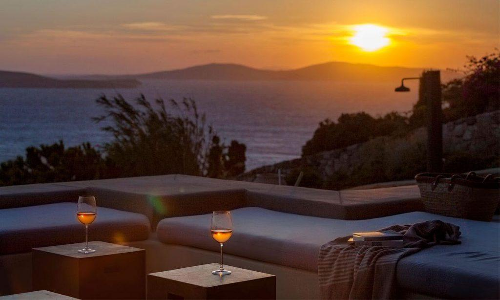 Villa-Agda_18.jpg Agios Ioannis Mykonos, outdoor, sunset, sofa, wine glasses, books, sea