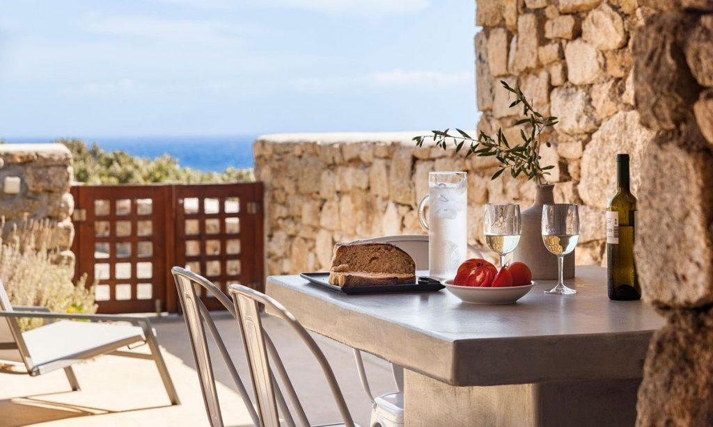 Villa-Agda_20.jpg Agios Ioannis Mykonos, outdoor dining area, dining table, wine, glasses, bread, tomato, sea, chairs