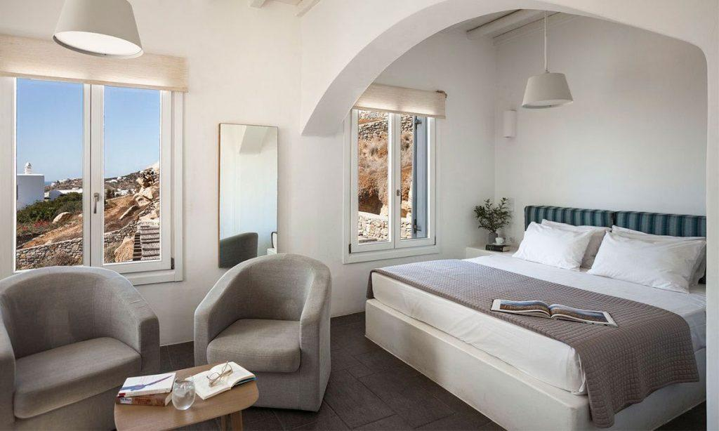 Villa-Agda_30.jpg Agios Ioannis Mykonos, 1st bedroom, king size bed, pillows, flowers, book, nightstand, window, mirror, armchairs, table, glass