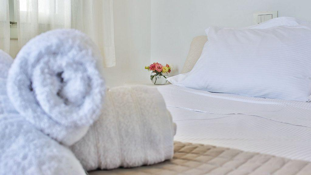 white wall bedroom with cozy bed and soft towels
