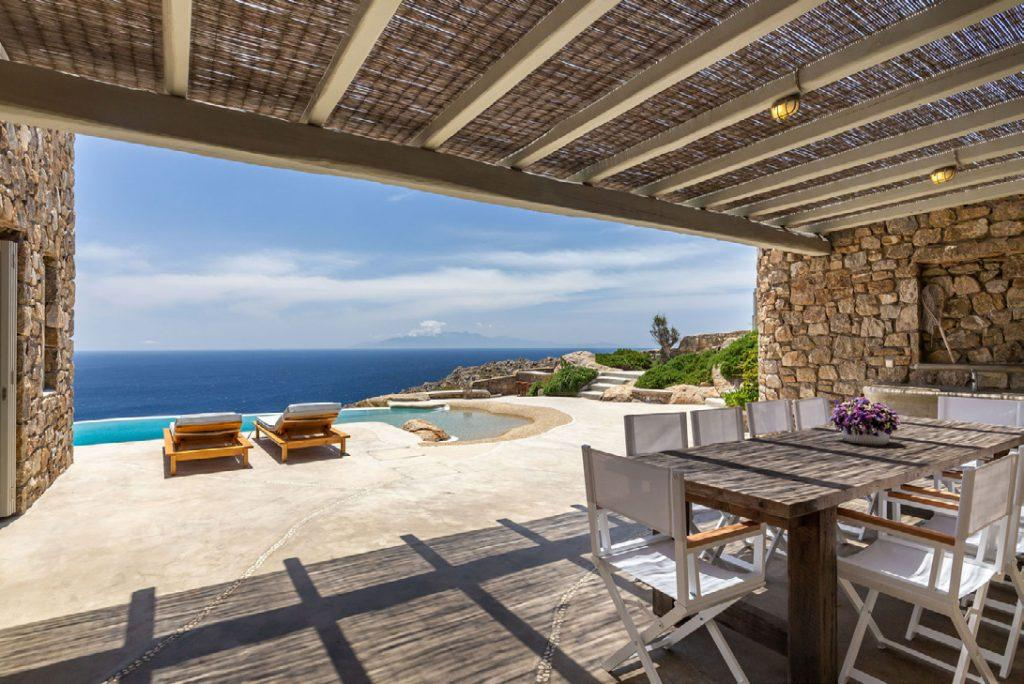 Villa-Camelia_14.jpg Agrari Mykonos, outdoor, dining table, chairs, climbers, pool, sea, sky, clouds