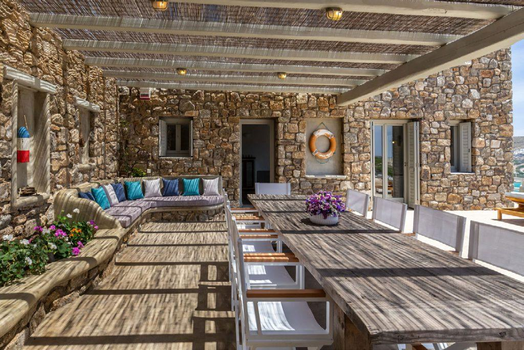 Villa-Camelia_16.jpg Agrari Mykonos, outdoor dining area, dining table, chairs, flowers, ,vase, sofa, pillows