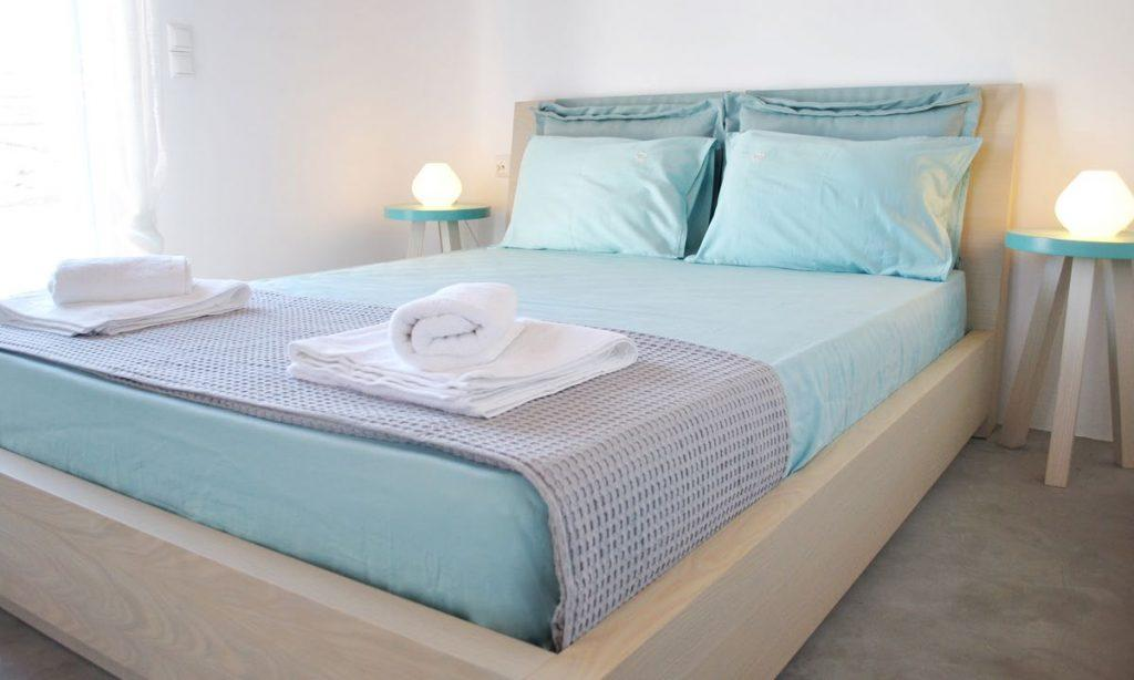 simply designed room with bluish linens and a comfortable bed