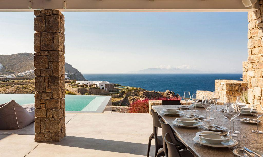 Villa-Paige-_12.jpg Elia Mykonos, outdoor, dining table, plates, sea, sky, clouds, sun bed, pool, glasses