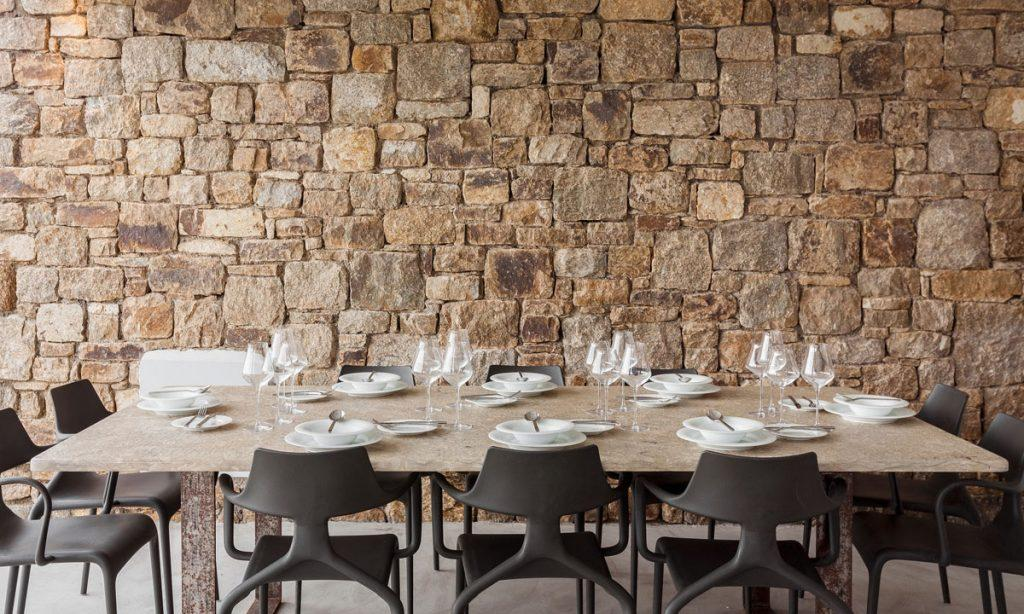 Villa-Paige-_13.jpg Elia Mykonos, dining table, plates, spoons, forks, knives, chair, stone wall