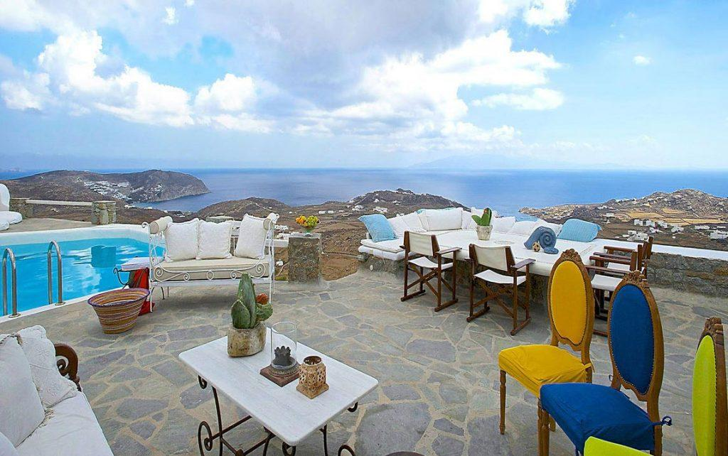 Villa-Ramsey-_10.jpg Halara Mykonos, outdoor, dining table, chairs, sofa, pillows, table, vase, flower, pool, sky, clouds, island