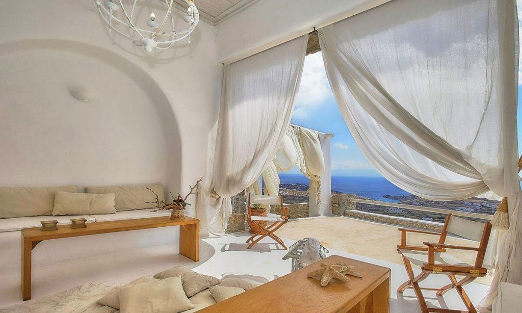 Villa-Ramsey-_14.jpg Halara Mykonos, living room, sofa, pillows, table, chairs, curtains, sea view