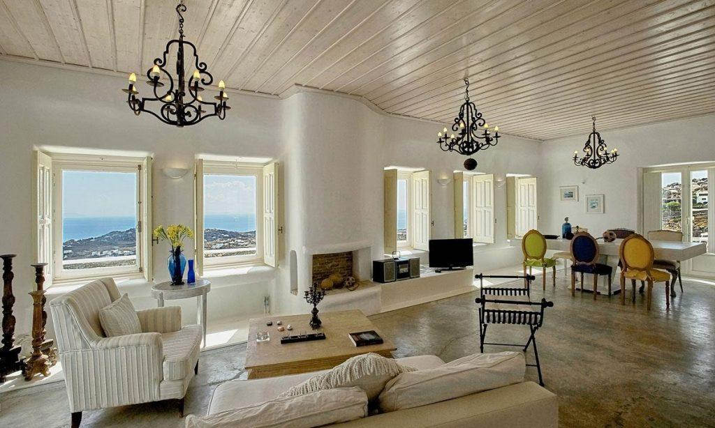 Villa-Ramsey-_16.jpg Halara Mykonos, living room, sofa, pillows, armchair, table, fireplace, chairs, dining table, windows, vase, flowers