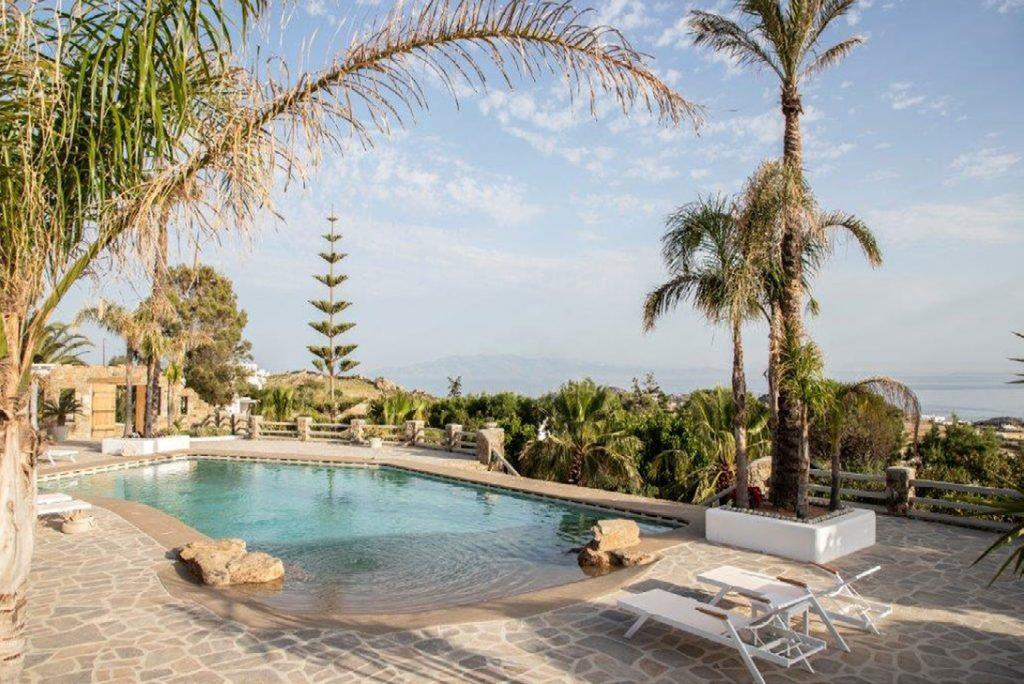 Villa-Sabina_07.jpg Kounoupas Mykonos, outdoor, pool, climbers, palms, trees, sea, sky ,clouds