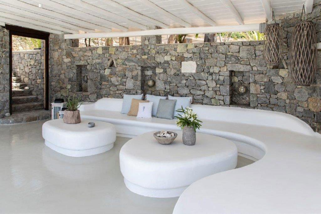 Villa-Sabina_15.jpg Kounoupas Mykonos, outdoor resting area, table, flowers, vase, sofa, pillows, stone wall