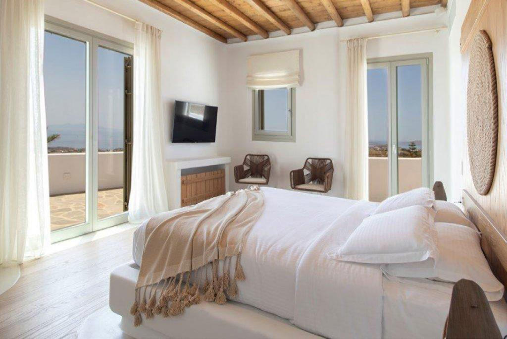 Villa-Sabina_32.jpg Kounoupas Mykonos, 3rd bedroom, king size bed, pillows, blanket, flat screen TV, curtains, chairs