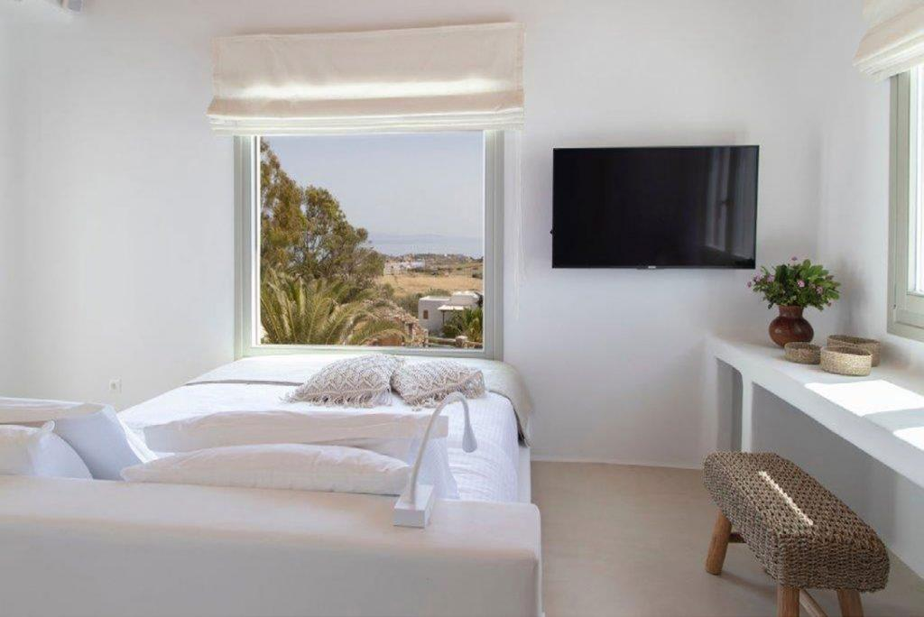Villa-Sabina_35.jpg Kounoupas Mykonos, bedroom, flat screen TV, chair, desk, flowers, vase, king size bed, pillows