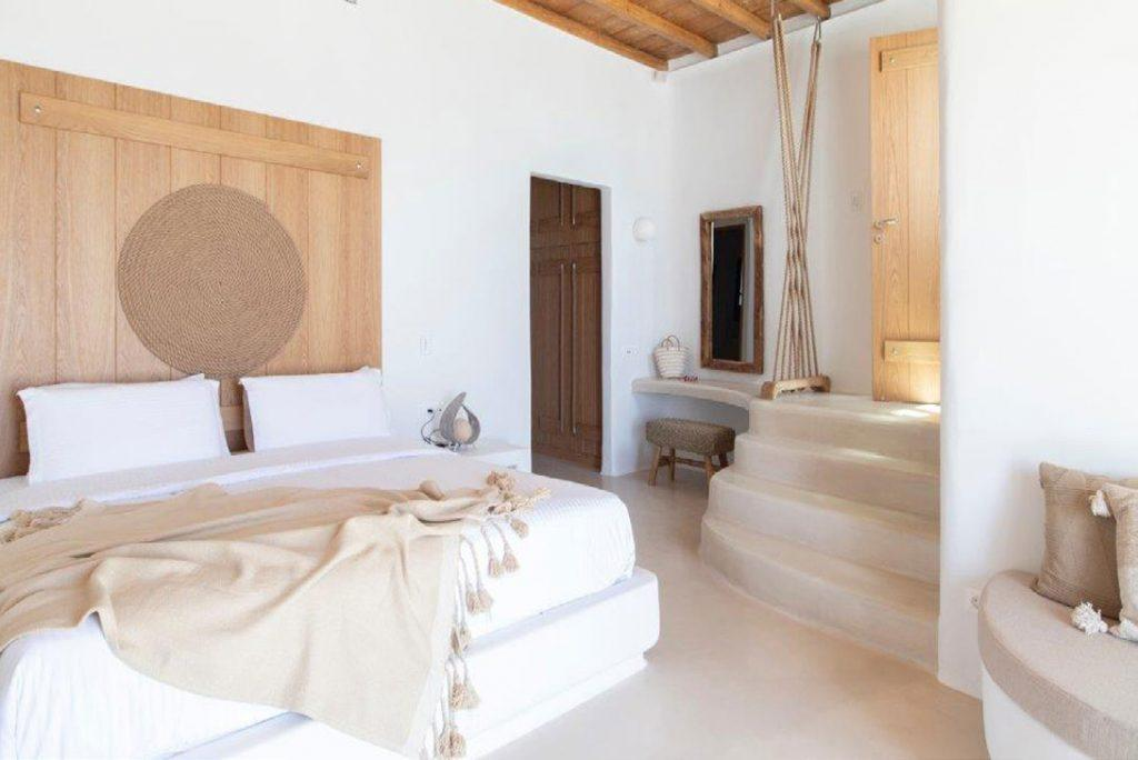 Villa-Sabina_37.jpg Kounoupas Mykonos 4th bedroom, king size bed, blanket, pillows, stairs, sofa, chair, mirror, desk