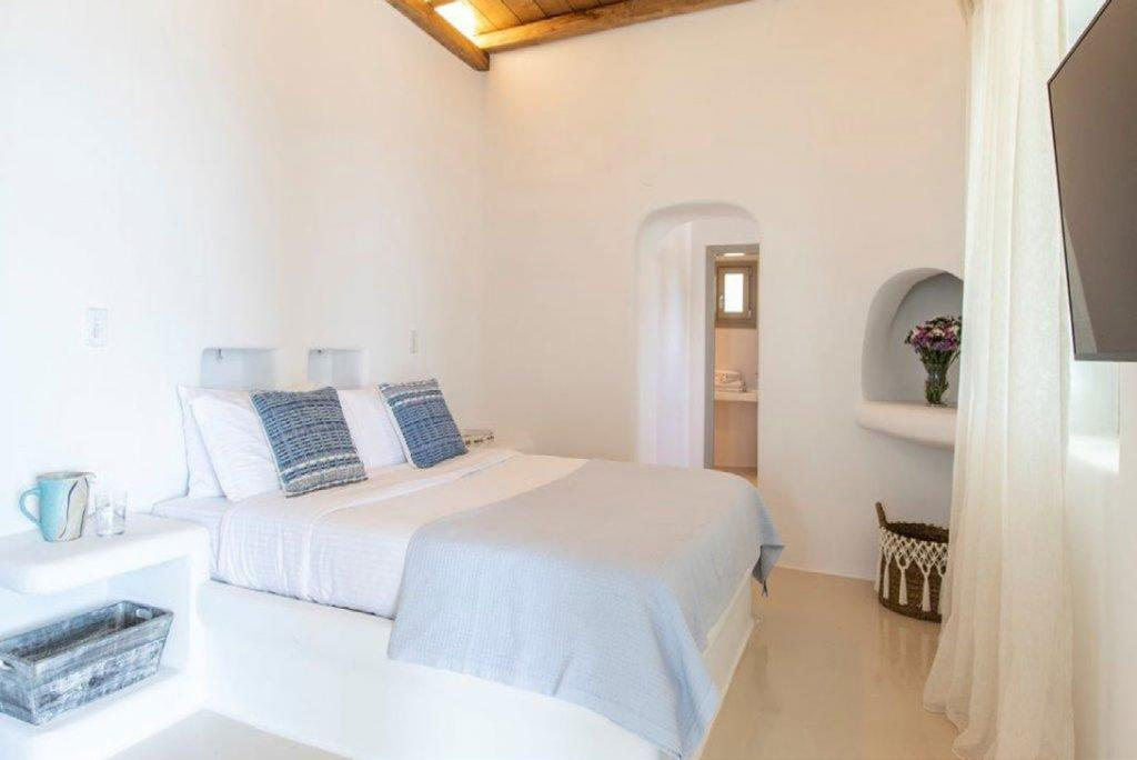 Villa-Sabina_45.jpg Kounoupas Mykonos, bedroom, flat screen TV, curtains, flowers, vase, pillows, nightstands, glass